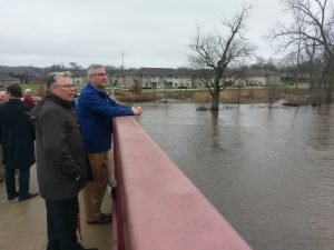 Photo of chancellor Allison and Governor Holcomb viewing floodwaters near campus.