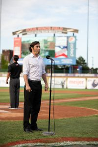 Photo of Emanuel Caraman from the Raclin School of the Arts singing the national anthem.